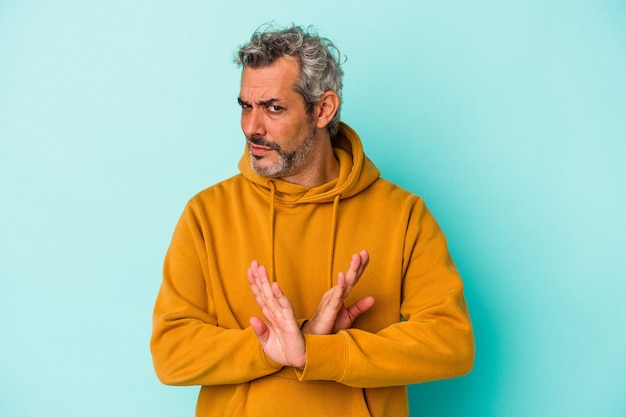 Kaukaski mężczyzna w średnim wieku na niebieskim tle robi gest odmowy