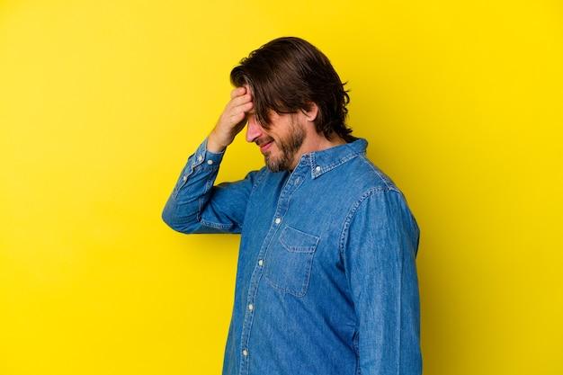 Kaukaski mężczyzna w średnim wieku, odizolowany na żółtej ścianie, mruga do aparatu przez palce, zawstydzony zakrywający twarz.