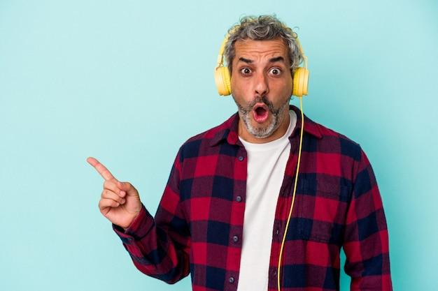 Kaukaski mężczyzna w średnim wieku słuchający muzyki na białym tle na niebieskim tle wskazujący na bok