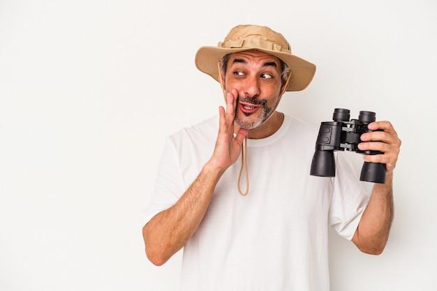 Kaukaski mężczyzna w średnim wieku trzymający lornetkę na białym tle mówi tajne gorące wiadomości o hamowaniu i patrząc na bok