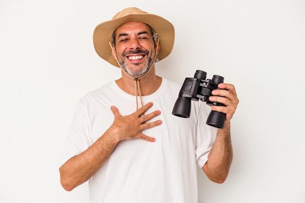 Kaukaski mężczyzna w średnim wieku trzymający lornetkę na białym tle śmieje się głośno trzymając rękę na klatce piersiowej.