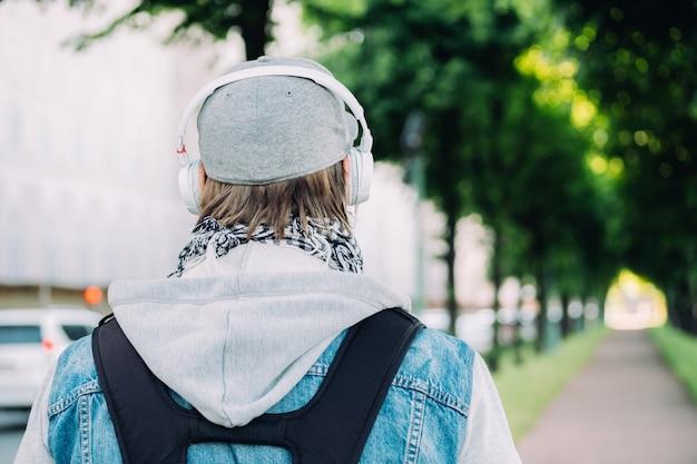 Kaukaski mężczyzna w szarej czapce idzie przez park ze słuchawkami