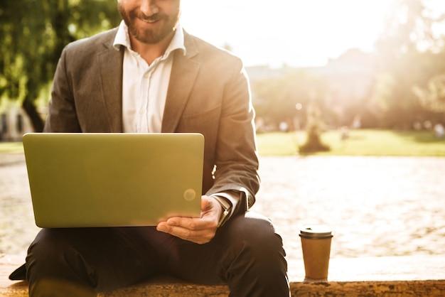 Kaukaski mężczyzna w szarym garniturze klasycznym, siedząc w parku z kawą na wynos podczas pracy na srebrnym laptopie