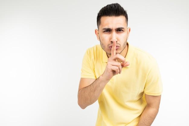 Kaukaski mężczyzna w żółtej koszulce prosi o ciszę