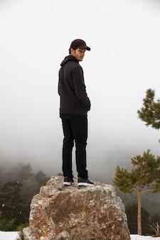 Kaukaski mężczyzna wspiął się na skałę w zaśnieżonym terenie górskim.