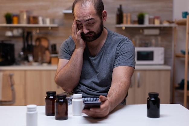 Kaukaski mężczyzna z bólem głowy patrzący na smartfona