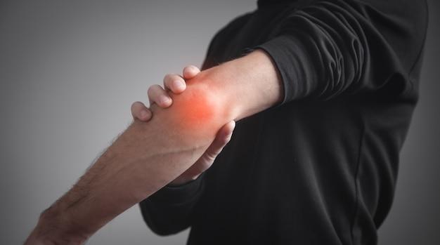 Kaukaski mężczyzna z bólem łokcia. koncepcja łagodzenia bólu