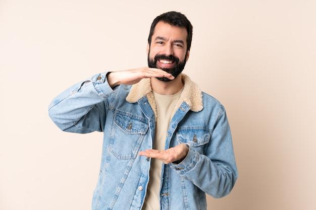 Kaukaski mężczyzna z brodą na białym tle gospodarstwa copyspace wyimaginowany na dłoni, aby wstawić reklamę