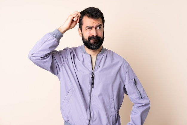 Kaukaski mężczyzna z brodą na sobie kurtkę na ścianie, mając wątpliwości podczas drapania głowy