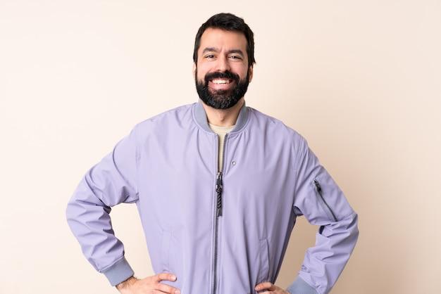 Kaukaski mężczyzna z brodą na sobie kurtkę na ścianie, pozowanie z rękami na biodrze i uśmiechnięty