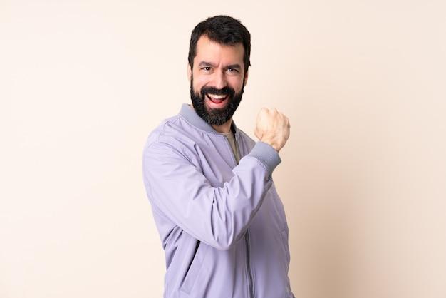 Kaukaski mężczyzna z brodą na sobie kurtkę na ścianie świętuje zwycięstwo
