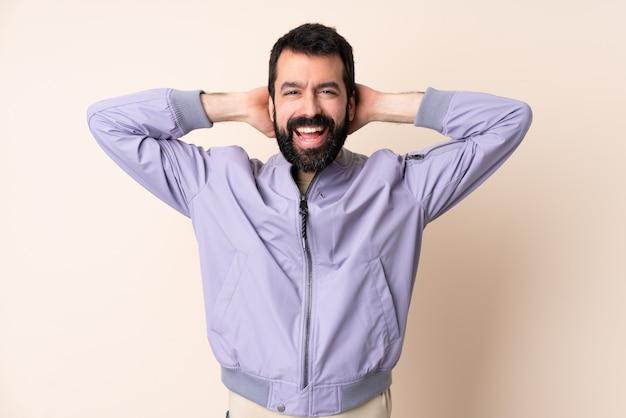 Kaukaski mężczyzna z brodą na sobie kurtkę na ścianie ze śmiechem