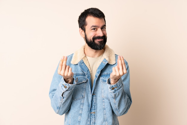 Kaukaski mężczyzna z brodą nad odosobnioną ścianą robi pieniądze gestowi