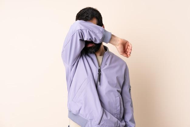 Kaukaski mężczyzna z brodą ubrany w kurtkę na białym tle zakrywający oczy rękami
