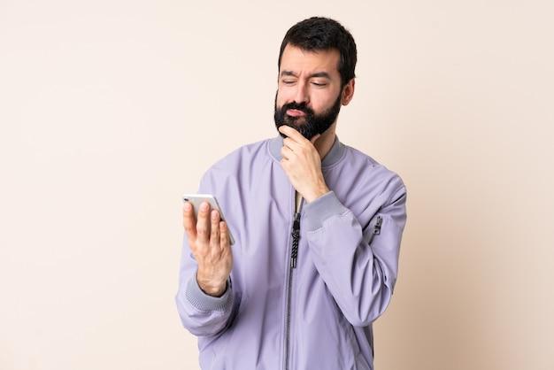 Kaukaski mężczyzna z brodą ubrany w kurtkę na odosobnionym tle myślący i wysyłający wiadomość
