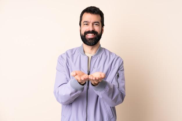 Kaukaski mężczyzna z brodą ubrany w marynarkę na białym tle gospodarstwa copyspace wyimaginowany na dłoni, aby wstawić reklamę