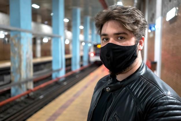 Kaukaski mężczyzna z brodą w czarnej masce medycznej, patrząc w kamerę w metrze