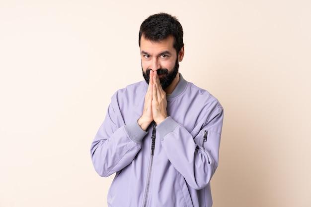 Kaukaski mężczyzna z brodą w kurtce na białym tle trzyma dłoń razem. osoba o coś prosi