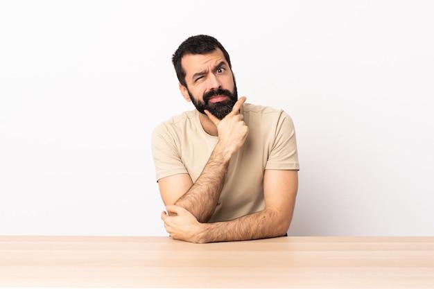 Kaukaski mężczyzna z brodą w stole ma wątpliwości.