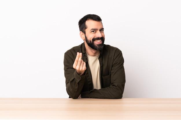 Kaukaski mężczyzna z brodą w stole robi pieniądze gestowi