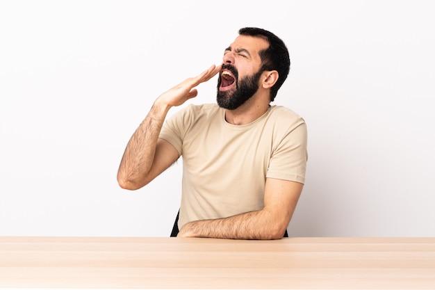Kaukaski mężczyzna z brodą w stole ziewanie i obejmujące ręką szeroko otwarte usta