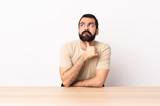Kaukaski mężczyzna z brodą w tabeli, mając wątpliwości i myślenie.