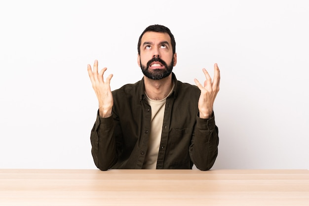 Kaukaski mężczyzna z brodą w tabeli podkreślił przytłoczony.