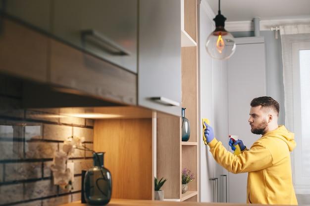 Kaukaski mężczyzna z brodą w żółtym swetrze sprząta dom w rękawiczkach i używa sprayu