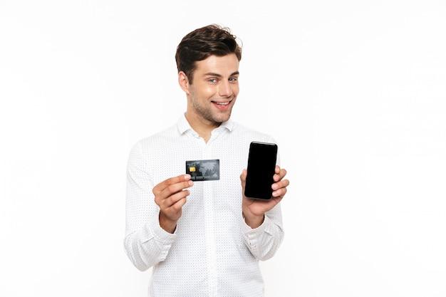 Kaukaski mężczyzna z ciemnymi włosami uśmiecha się trzymając smartfon i kartę kredytową