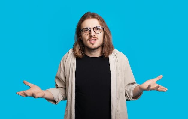 Kaukaski mężczyzna z długimi włosami i brodą patrzy przez okulary i gestem pyta na niebieskiej ścianie