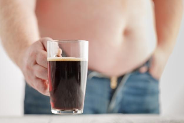 Kaukaski mężczyzna z fat beer belly, trzymający szklankę ciemnego piwa. dżinsy są bardzo obcisłe