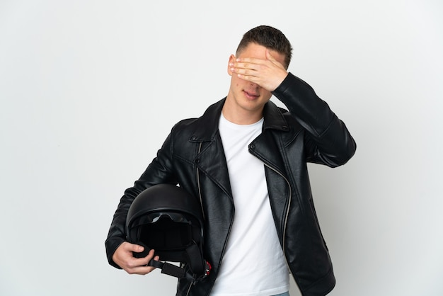 Kaukaski mężczyzna z kaskiem motocyklowym na białym tle na białym tle zasłaniając oczy rękami. nie chcę czegoś widzieć