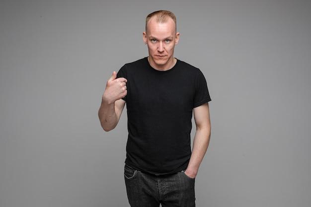 Kaukaski mężczyzna z krótkimi jasnymi włosami, ubrany w czarny t-shirt i dżinsy, wskazuje na siebie palcem
