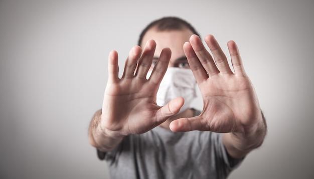 Kaukaski mężczyzna z maską medyczną robi gest stopu.