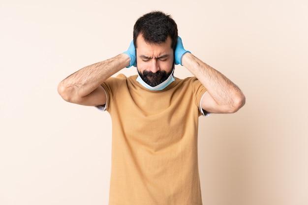 Kaukaski mężczyzna z ochroną brody z maską i rękawiczkami na izolowanej ścianie sfrustrowany i obejmujące uszy