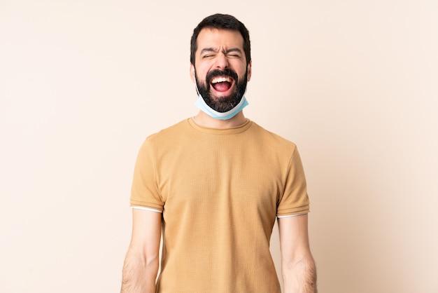 Kaukaski mężczyzna z ochroną brody z maską i rękawiczkami na ścianie krzyczy do przodu z szeroko otwartymi ustami