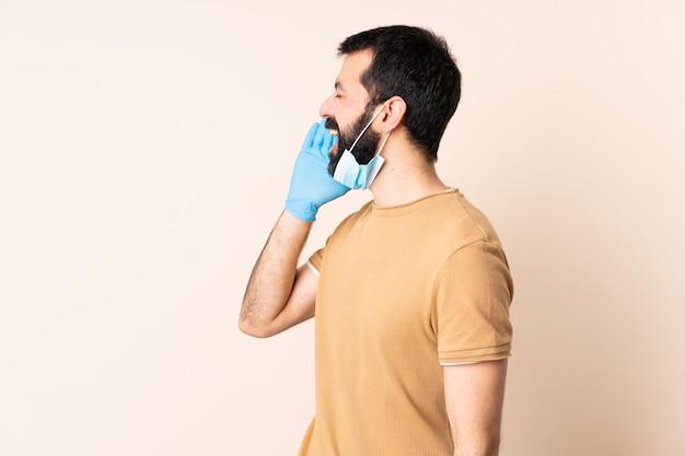 Kaukaski mężczyzna z ochroną brody z maską i rękawiczkami na ścianie krzyczy z szeroko otwartymi ustami z boku