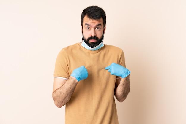 Kaukaski mężczyzna z ochroną brody z maską i rękawiczkami na ścianie, wskazując na siebie