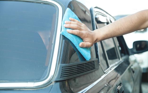 Kaukaski mężczyzna z szmatką do czyszczenia samochodu.