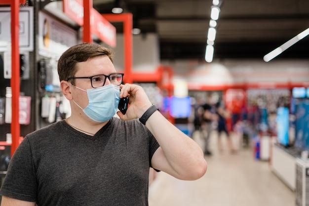 Kaukaski mężczyzna zakupy ubrań z maską medyczną. nowa normalna koncepcja.