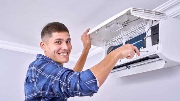 Kaukaski mistrz w niebieskiej koszuli czyści filtry, instaluje i naprawia klimatyzator w pomieszczeniach
