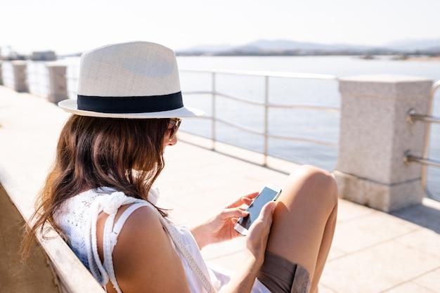 Kaukaski młoda kobieta w białym kapeluszu siedzi na ławce na chodniku nad morzem za pomocą swojego smartfona