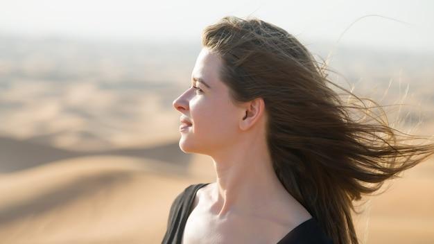 Kaukaski młoda kobieta z długimi włosami w czarnej sukni o wschodzie słońca na pustyni
