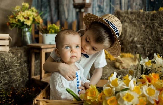 Kaukaski młodszy brat i siostra przytulają się w wielkanocnych dekoracjach. wielkanoc dla dzieci