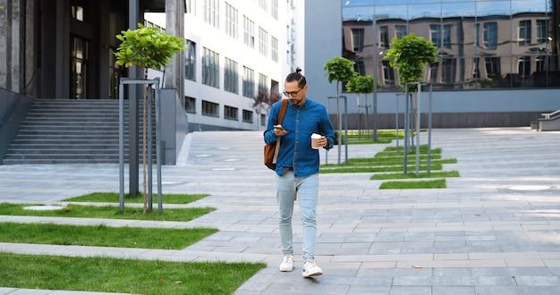 Kaukaski młody człowiek idzie schodami w dół ulicy, dotykając smartfona i popijając drinka. mężczyzna schodzący po drabinie na zewnątrz, wysyłający sms-y przez telefon i pijący kawę na wynos. pośpiech rano.