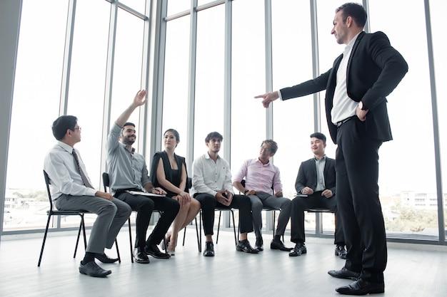 Kaukaski młody człowiek oferujący informacje osobom w zespole w spotkaniach i planowaniu pracy