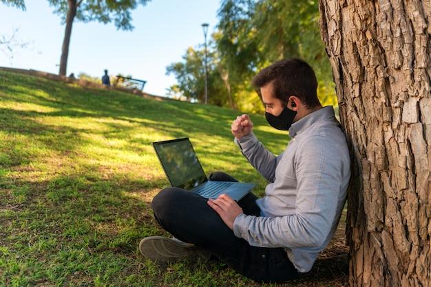Kaukaski młody człowiek siedzący na trawie, oglądając mecz na laptopie za pomocą laptopa w pięknym parku w słoneczny dzień.