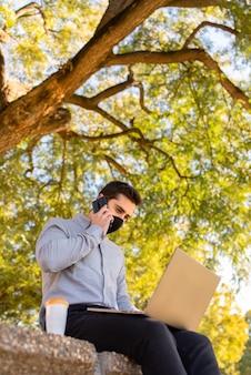 Kaukaski młody człowiek ubrany w maskę, pracujący i studiujący w inżynierii, rozmawiając przez telefon i używając swojego laptopa w pięknym parku w słoneczny dzień.