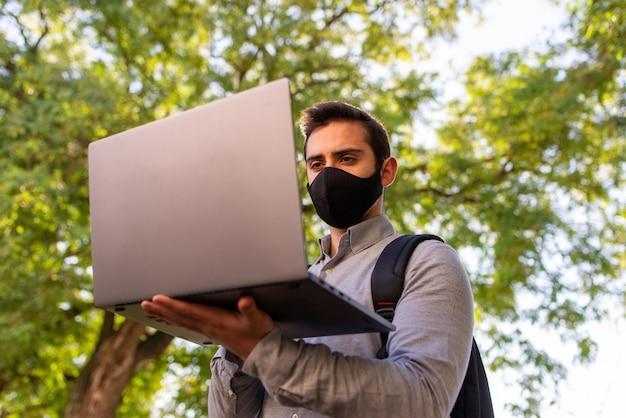 Kaukaski młody człowiek ubrany w maskę pracuje i studiuje w inżynierii za pomocą swojego laptopa w pięknym parku w słoneczny dzień