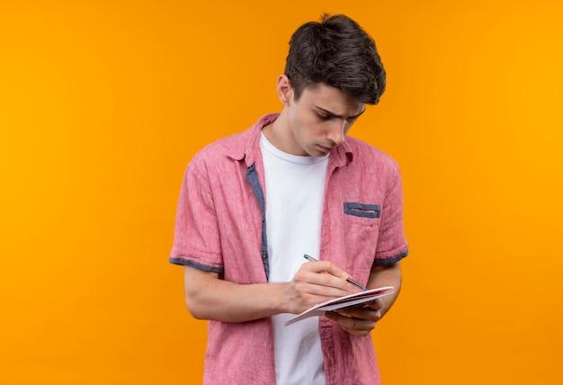 Kaukaski młody człowiek ubrany w różową koszulę pisze piórem w notesie na odizolowanych pomarańczowej ścianie